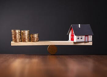 Haus und Geld auf der Waage im Einklang